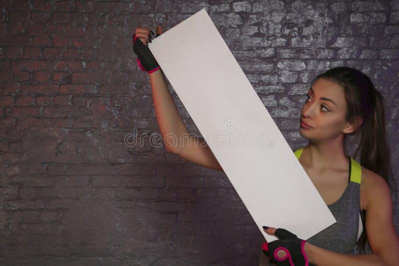 Belle jeune fille tenant un conseil vide, l'espace de copie pour annoncer, les muscles et le gymnase, photo conceptuelle, espace  photographie stock