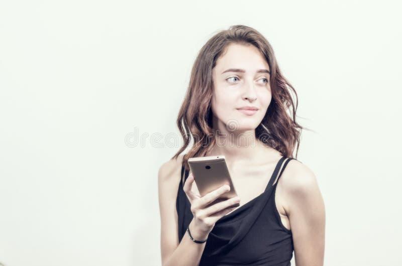 Belle jeune fille tenant un téléphone Fait des photos, selfies photographie stock libre de droits