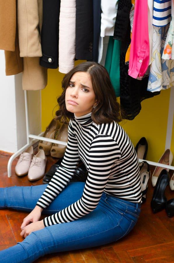 Belle jeune fille triste s'asseyant sous ses vêtements et chaussures image libre de droits