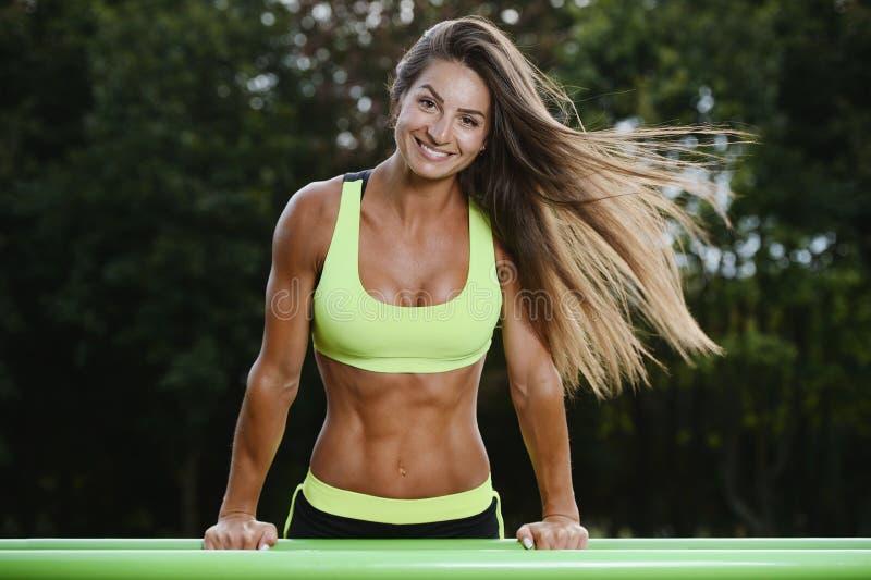 Belle jeune formation caucasienne musculaire sportive forte de séance d'entraînement de femme de forme physique de sport en plein photo libre de droits