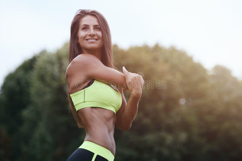 Belle jeune formation caucasienne musculaire sportive forte de séance d'entraînement de femme de forme physique de sport en plein image stock