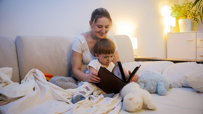 Belle jeune histoire pour endormir de lecture de mère à son fils d'enfant en bas âge images libres de droits