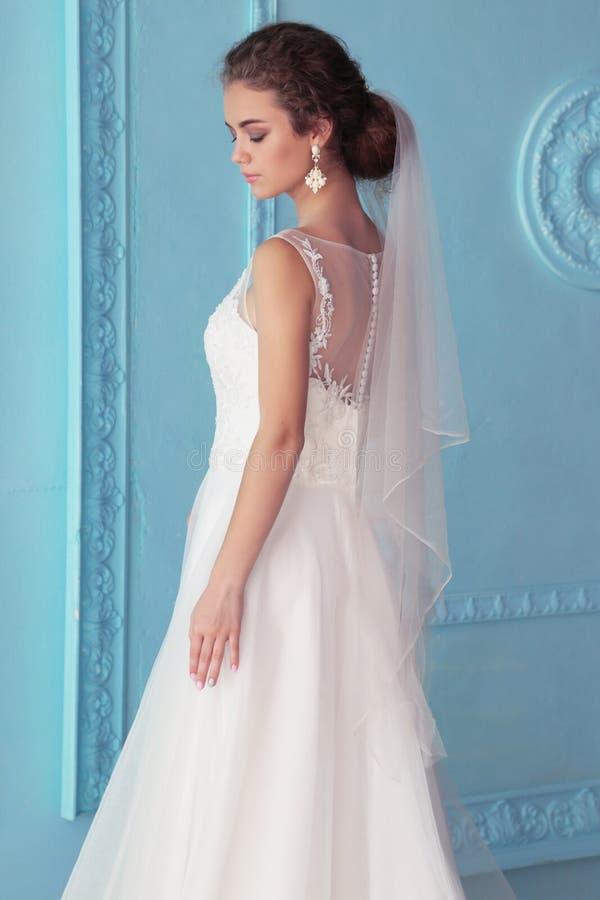 Belle jeune jeune mariée avec les cheveux bouclés sombres dans la robe de mariage luxueuse posant à la pièce photo stock