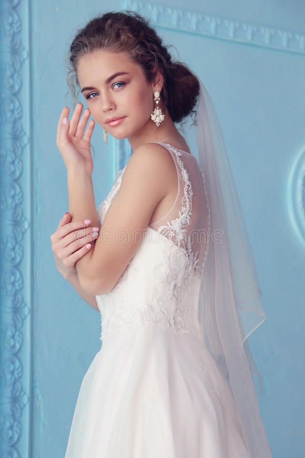 Belle jeune jeune mariée avec les cheveux bouclés sombres dans la robe de mariage luxueuse posant à la pièce images stock