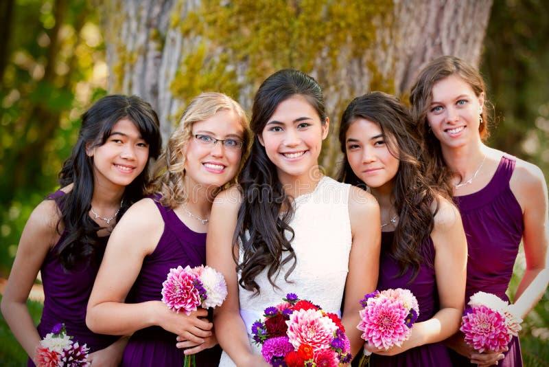 Belle jeune jeune mariée biracial souriant avec son grou multi-ethnique photographie stock