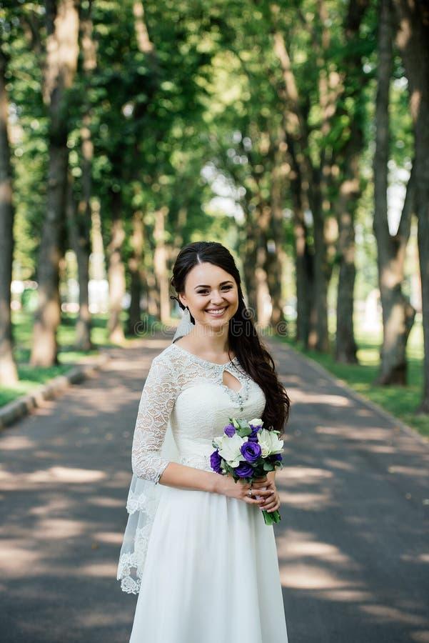 Belle jeune jeune mariée de sourire de brune dans la robe de wedd avec le bouquet des fleurs dans des mains dehors sur le fond de image stock