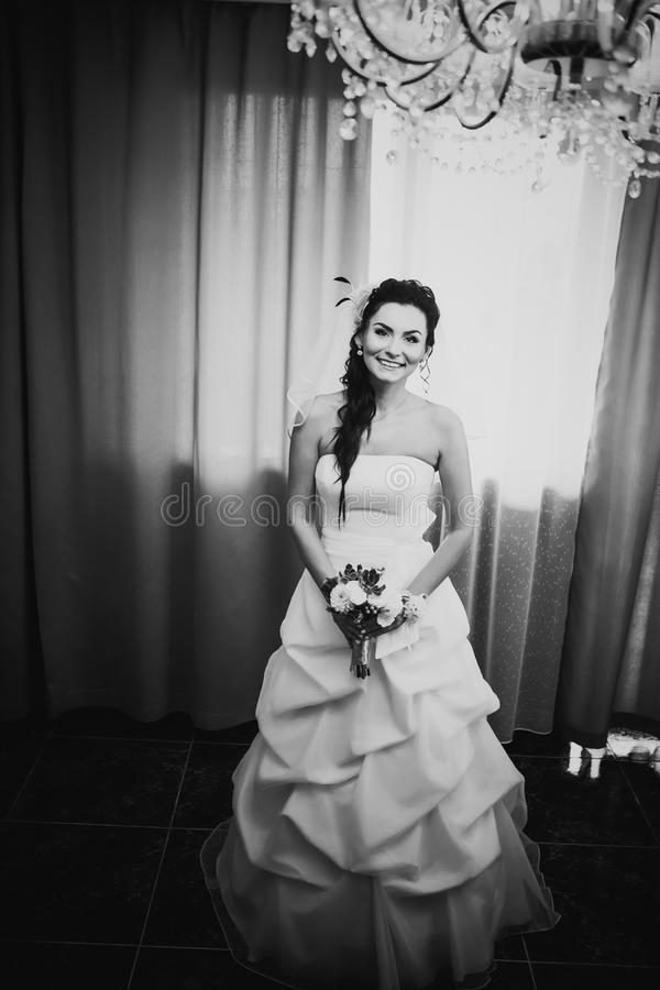 Belle jeune jeune mariée heureuse de photographie blanche noire se tenant près de la fenêtre image stock