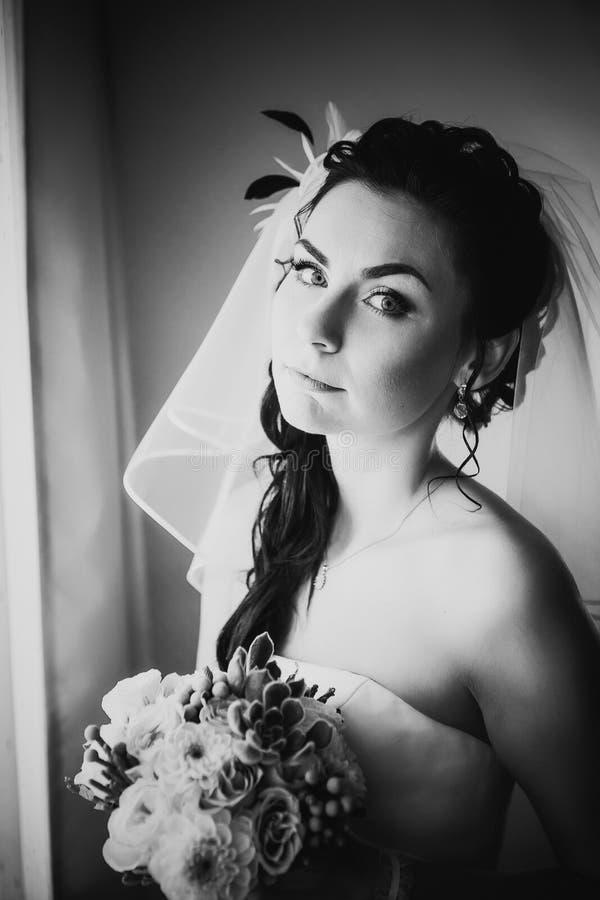 Belle jeune jeune mariée heureuse de photographie blanche noire se tenant près de la fenêtre photographie stock libre de droits