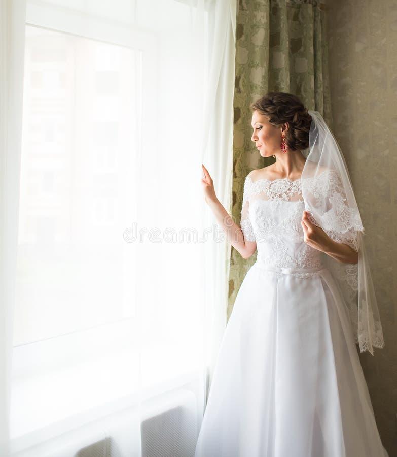 Belle jeune jeune mariée se tenant près d'une attente de fenêtre photos stock