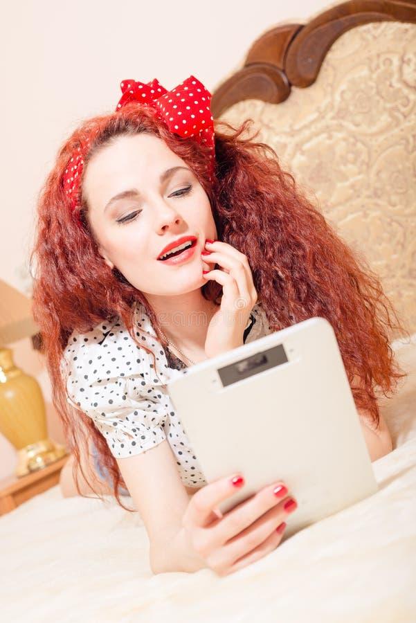 Belle jeune lecture rousse de femme avec le comprimé images stock