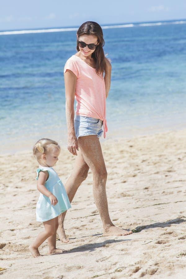 Belle jeune mère avec son petit dérivé marchant le long du Th photographie stock libre de droits