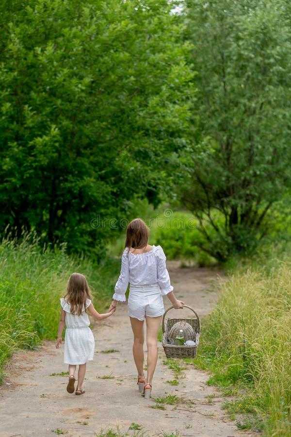 Belle jeune mère et sa petite fille dans la robe blanche ayant l'amusement dans un pique-nique Ils marchent le long de la route e images libres de droits