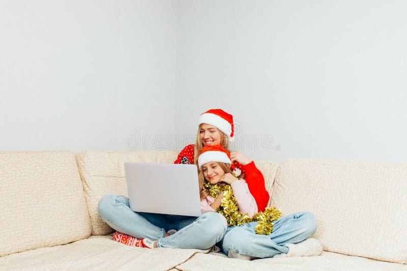 Belle jeune mère et sa petite fille habillées dans Santa image libre de droits
