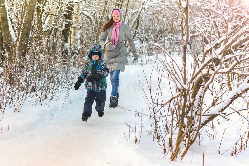 Belle jeune mère marchant avec son fils dans le rattrapage de jeu de forêt d'hiver image libre de droits