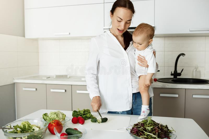 Belle jeune mère tenant le petit fils sur des mains dans la cuisine lui montrant comment couper des légumes pour la salade Regard images libres de droits