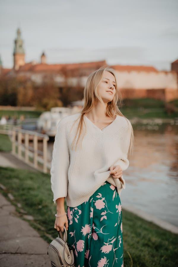 Belle jeune marche blonde le long du remblai près de la rivière et pose au coucher du soleil en été photos libres de droits