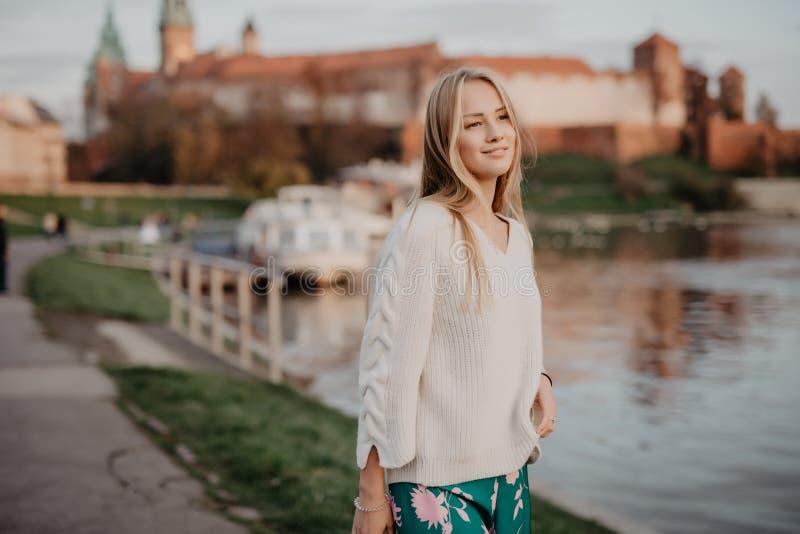 Belle jeune marche blonde le long du remblai près de la rivière et pose au coucher du soleil en été images libres de droits