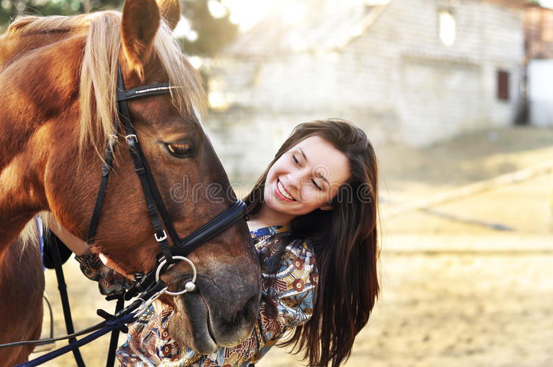 Belle jeune marche femelle et caresse de son cheval brun dans une campagne photo libre de droits