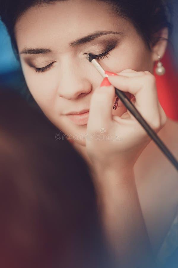 Belle jeune mariée appliquant le maquillage de mariage par l'artiste de maquillage professionnel image stock