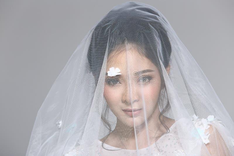 Belle belle jeune mariée asiatique de femme dans la robe blanche W de robe de mariage photographie stock libre de droits