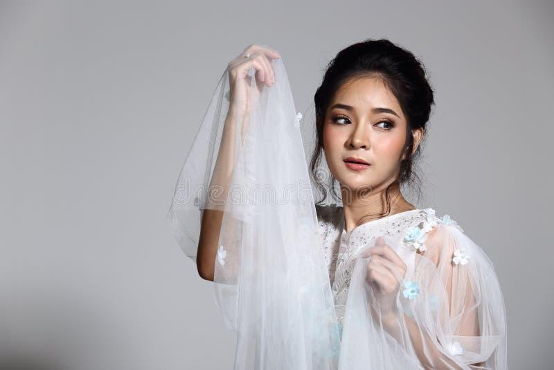 Belle belle jeune mariée asiatique de femme dans la robe blanche W de robe de mariage images libres de droits