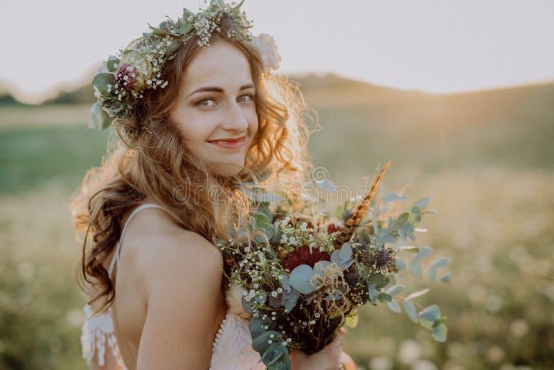 Belle jeune jeune mariée au coucher du soleil en nature verte photographie stock