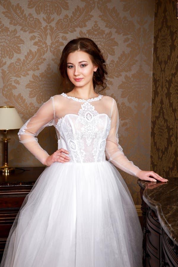 Belle jeune jeune mariée avec des poils de brune dans une chambre à coucher Robe de mariage blanche classique Fermez-vous vers le image stock