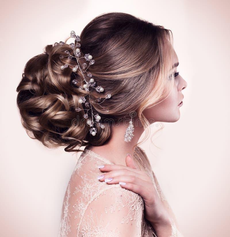 Belle jeune mariée avec la coiffure de mariage de mode - sur le fond beige photographie stock libre de droits