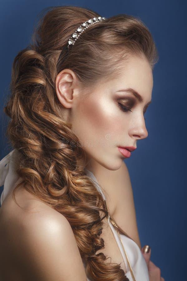 Belle jeune mariée avec la coiffure de mariage de mode - sur le fond bleu photos stock