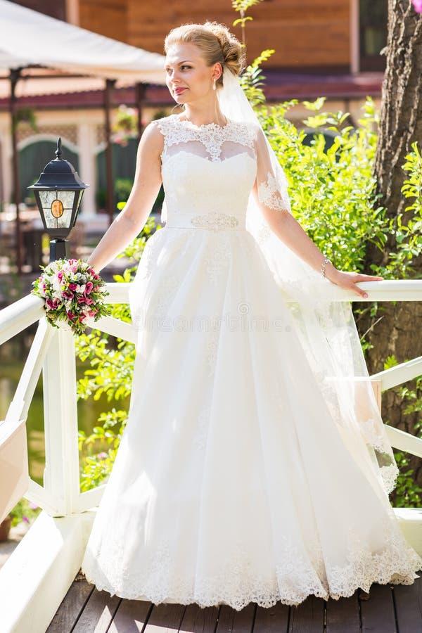 Belle jeune mariée avec le bouquet des fleurs extérieures images stock