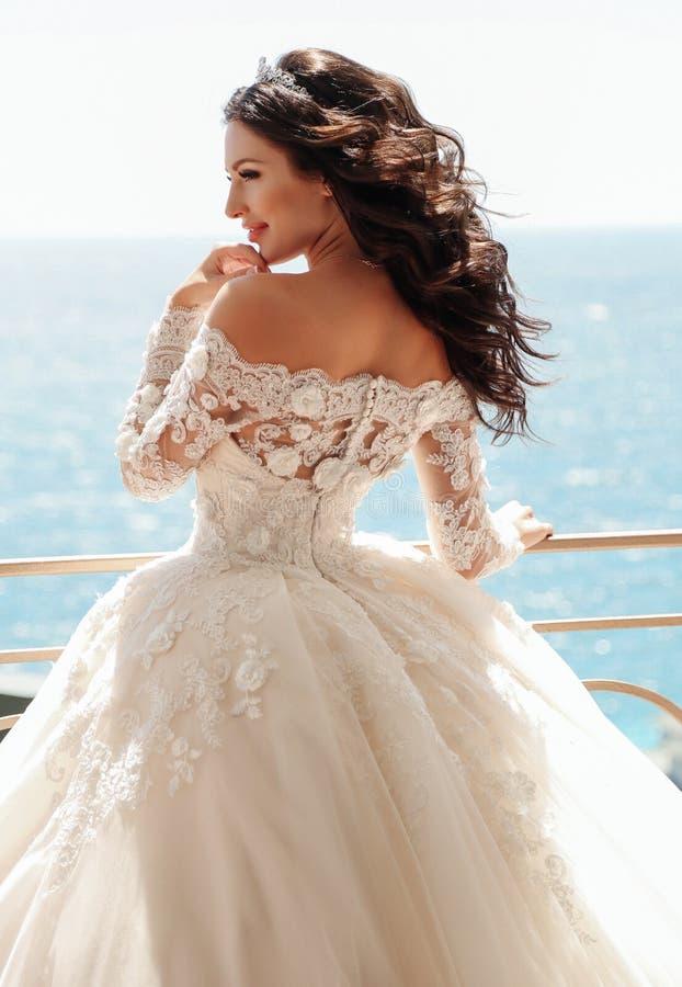 Belle jeune mariée avec les cheveux foncés dans la robe de mariage luxueuse images stock