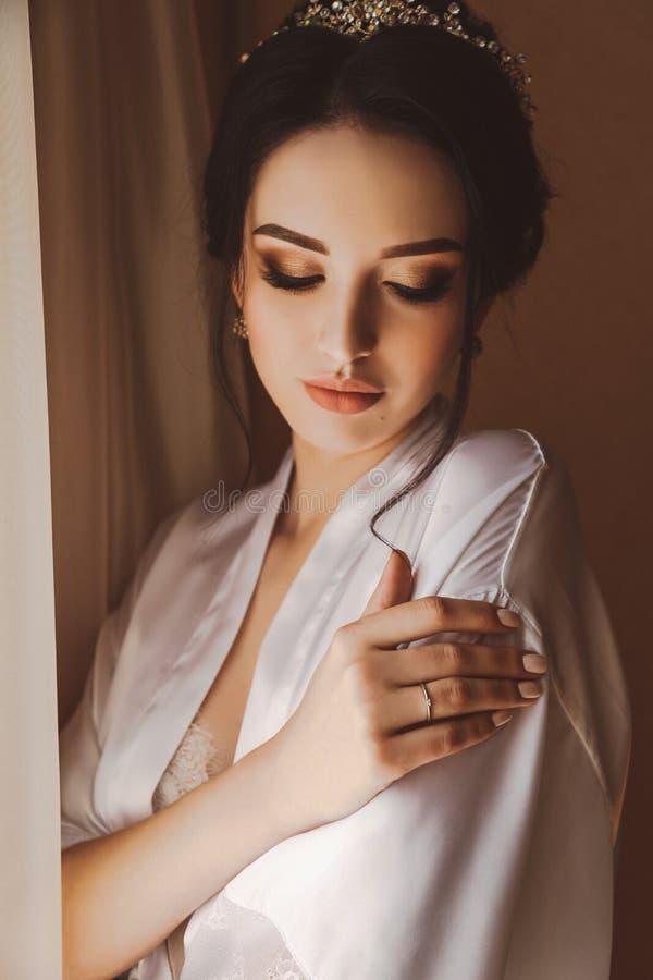 Belle jeune mariée avec les cheveux foncés se préparant dans son mariage photographie stock libre de droits