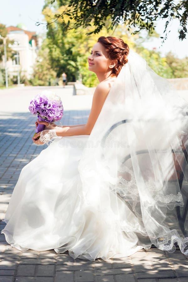Belle jeune mariée avec les cheveux rouges dans une robe l'épousant blanche et un long voile se reposant sur un banc de parc, rec image stock
