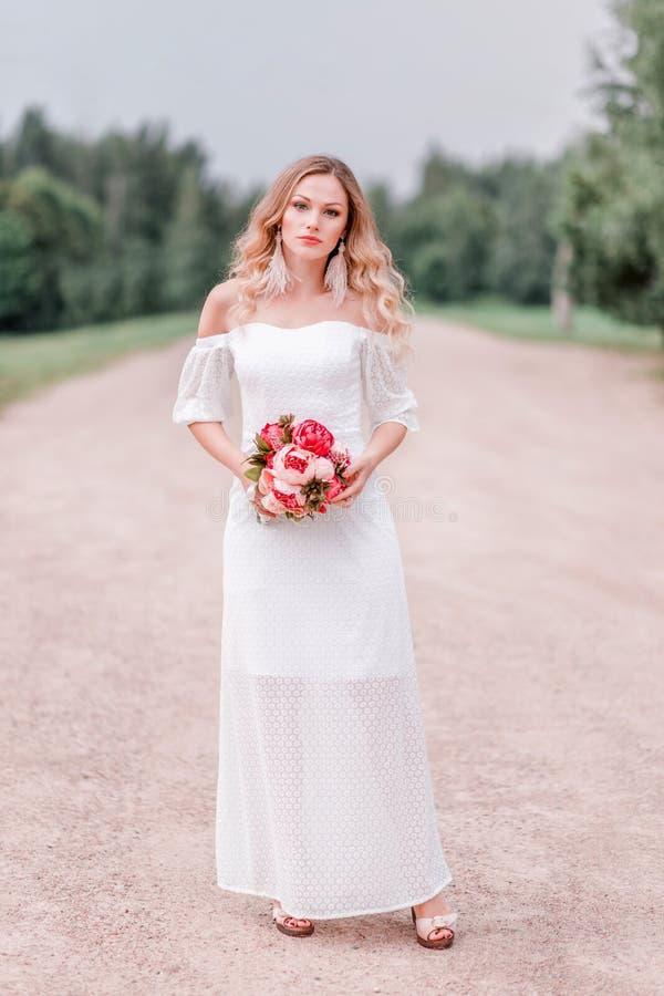 Belle jeune mariée avec un bouquet des fleurs dans la perspective de la route images stock