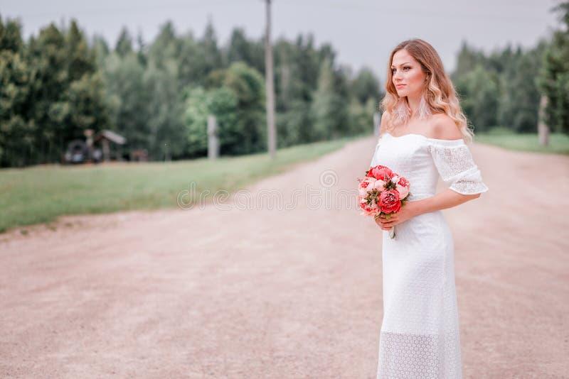 Belle jeune mariée avec un bouquet des fleurs dans la perspective de la route photo libre de droits
