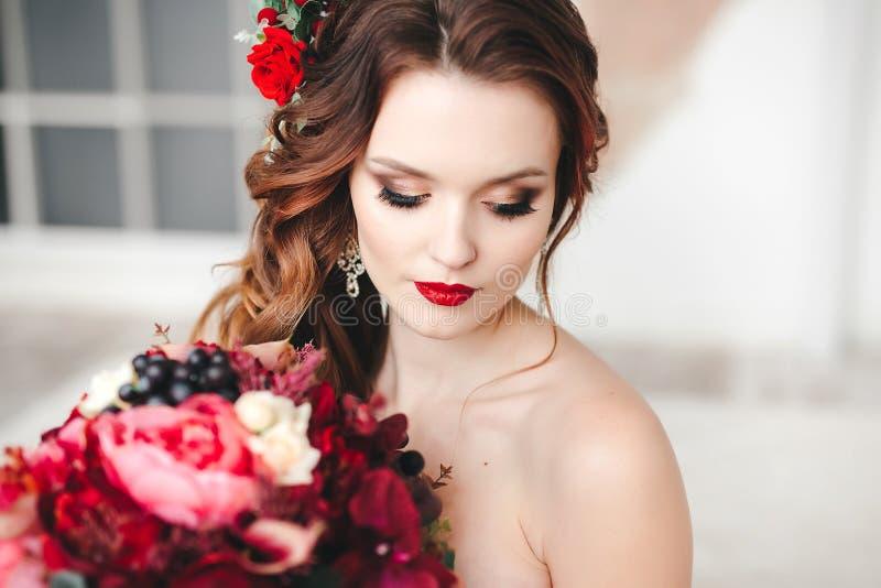 Belle jeune mariée avec un bouquet l'épousant original dans un intérieur de cru images libres de droits