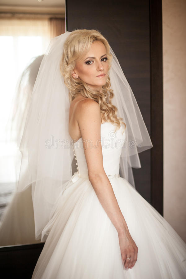 Belle jeune mariée blonde élégante magnifique pendant le matin dans le RO photographie stock