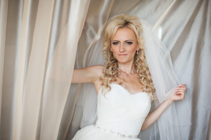 Belle jeune mariée blonde élégante magnifique sous Tulle près d'un windo image stock