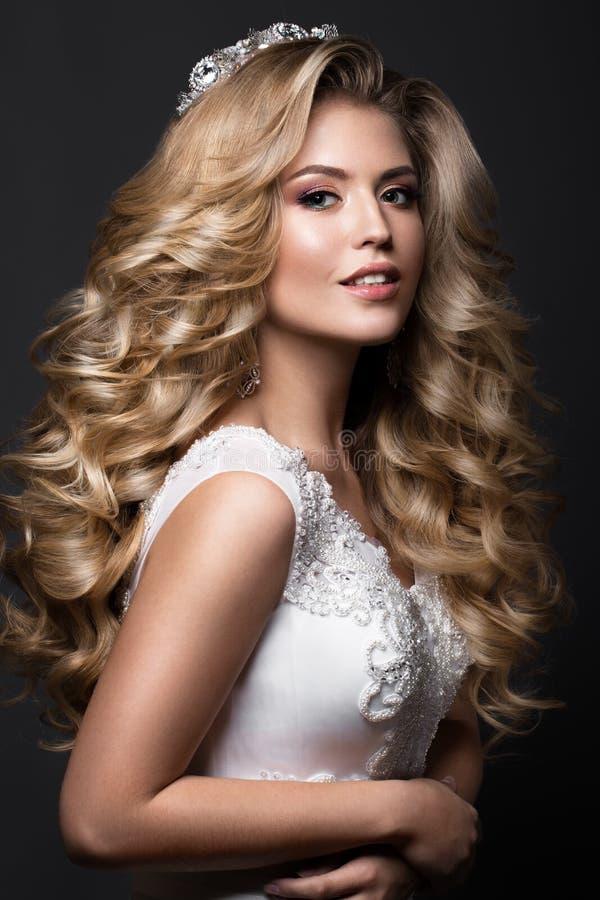 Belle jeune mariée blonde dans l'image de mariage avec les boucles et la couronne Visage de beauté photo libre de droits