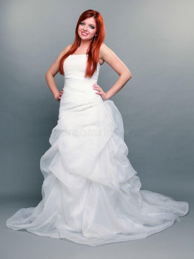 Belle jeune mariée d'une chevelure rouge heureuse sur le fond gris image stock