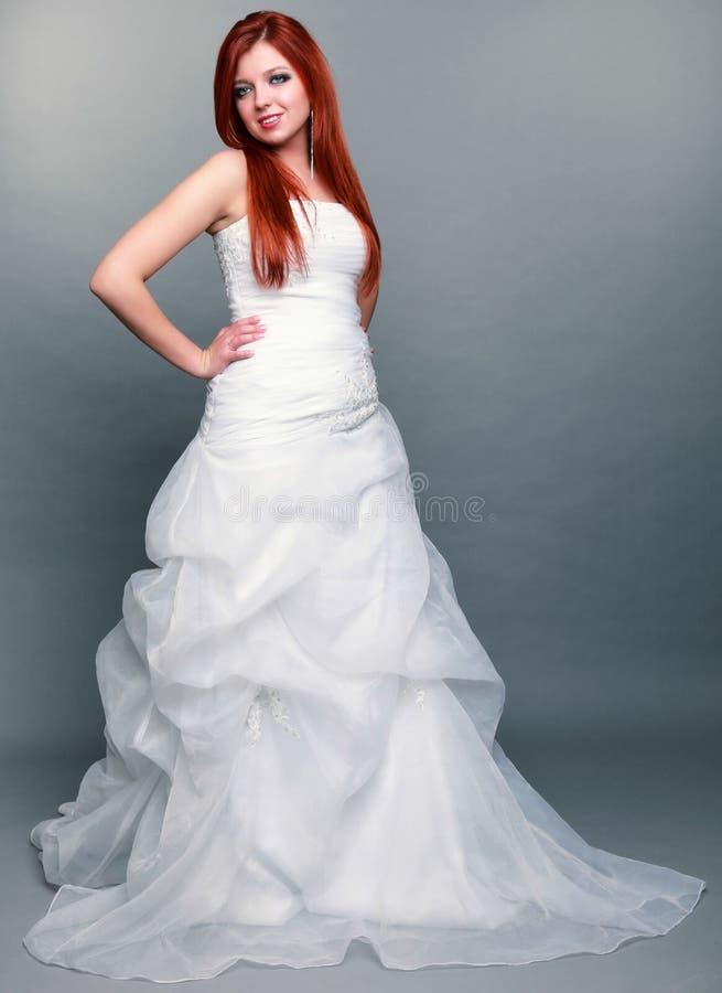 Belle jeune mariée d'une chevelure rouge heureuse sur le fond gris photographie stock libre de droits