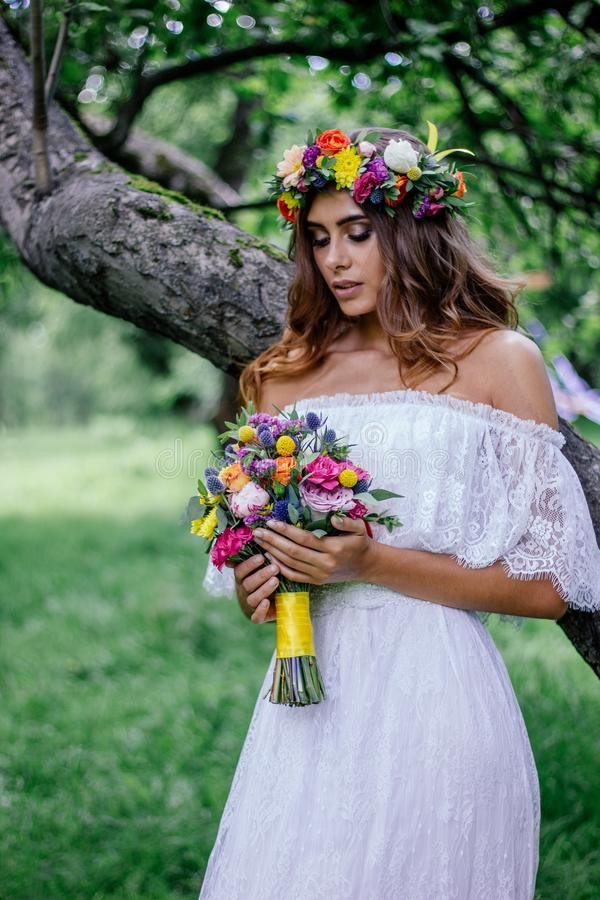 Belle jeune mariée dans la forêt verte près du vieil arbre photos libres de droits