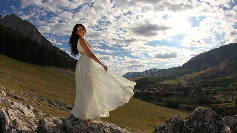 Belle jeune mariée dans la longue robe blanche en nature photographie stock libre de droits