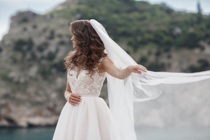 Belle jeune mariée dans la robe blanche posant sur la mer et les montagnes à l'arrière-plan photos libres de droits
