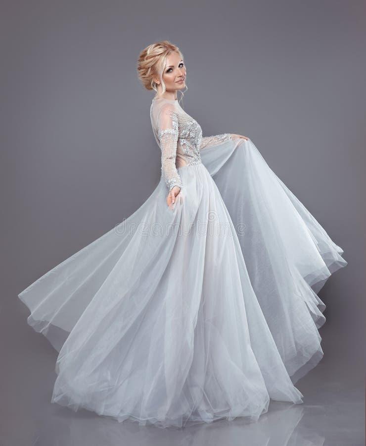 Belle jeune mariée dans la robe débordante de mousseline de soie de mariage, femme dedans longtemps photo stock