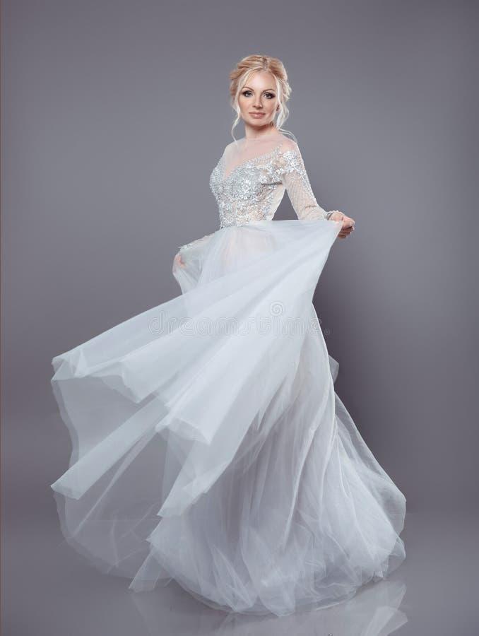 Belle jeune mariée dans la robe débordante de mousseline de soie de mariage, femme dedans longtemps image stock