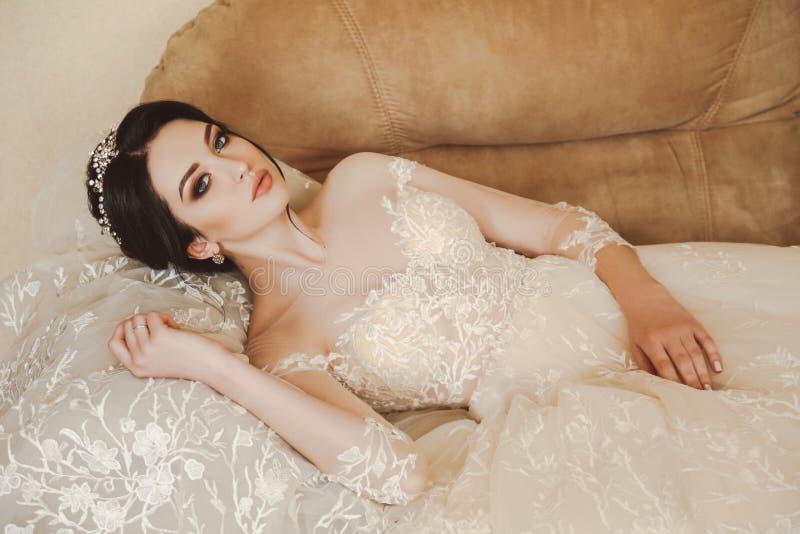 Belle jeune mariée dans la robe de mariage élégante et diadème posant dans r photo stock