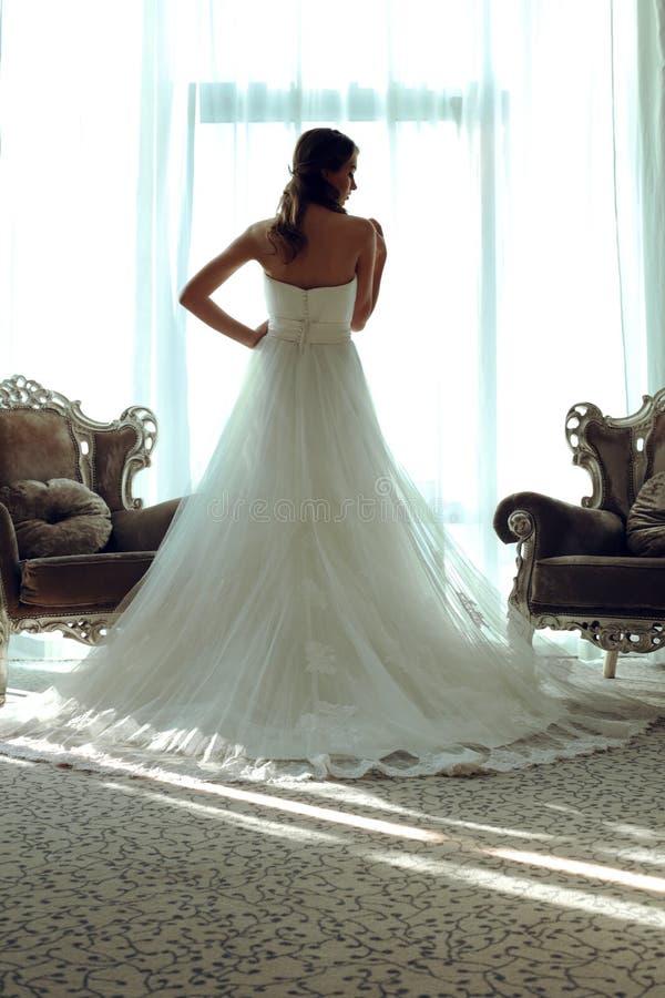 Belle jeune mariée dans la robe de mariage élégante posant dans la chambre à coucher, vue arrière photo stock
