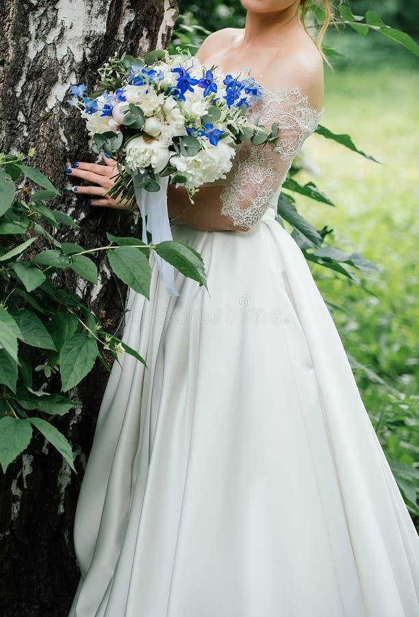Belle jeune mariée dans la robe de mariage avec le bouquet de mariage des pivoines photo stock