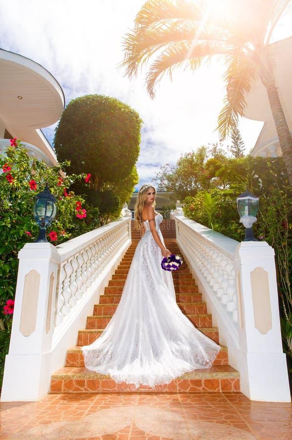 Belle jeune mariée dans la robe de mariage avec le long train se tenant sur photos libres de droits